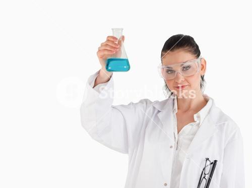 Darkhaired scientist holding a blue flask