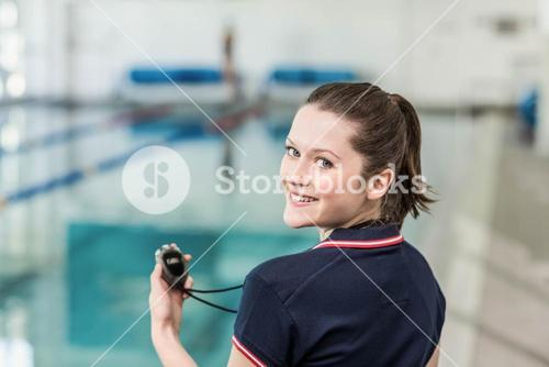 Pretty trainer holding at stopwatch