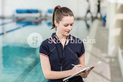 Pretty trainer writing on clipboard