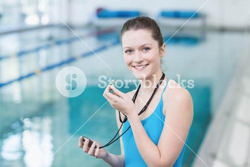Pretty trainer blowing whistle and looking at stopwatch