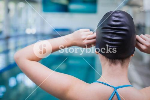 Rear view of fit woman putting on swim cap