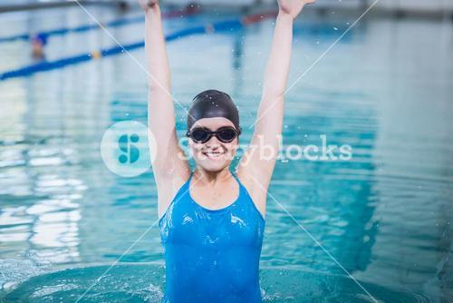 Fit woman triumphing with raised arms