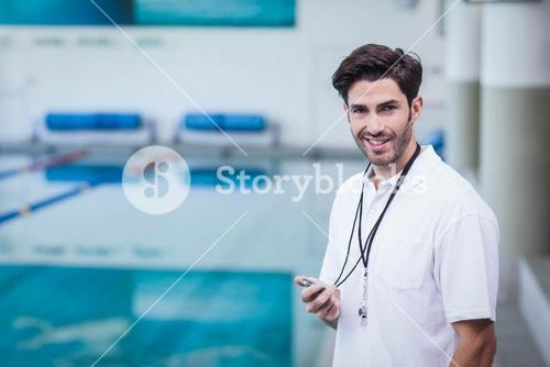Handsome trainer holding stopwatch