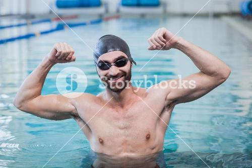Smiling man triumphing with raised arms
