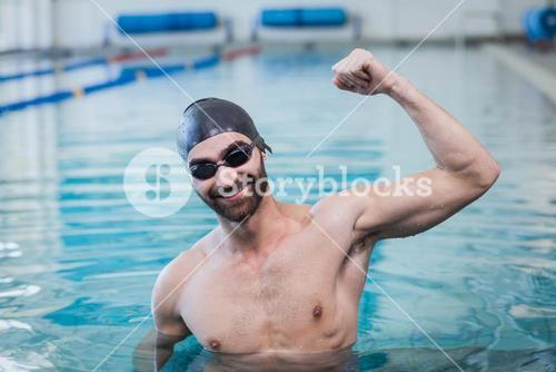 Smiling man triumphing with raised arm