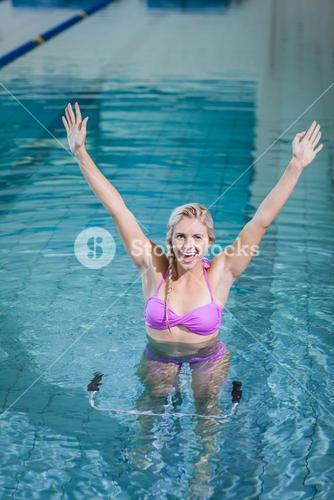 Fit woman doing underwater bike with raised arms