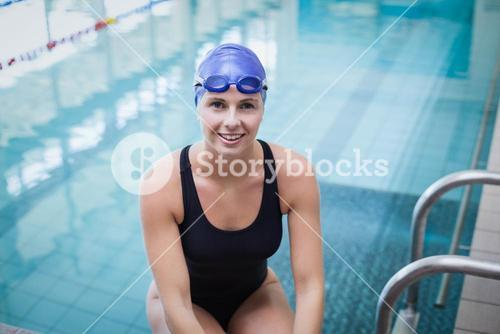 Pretty woman wearing swim cap and goggles