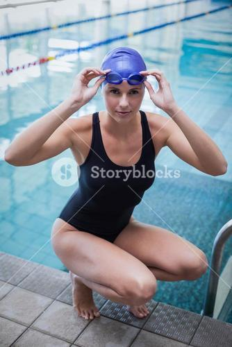 Pretty woman crouching and wearing swim cap and goggles