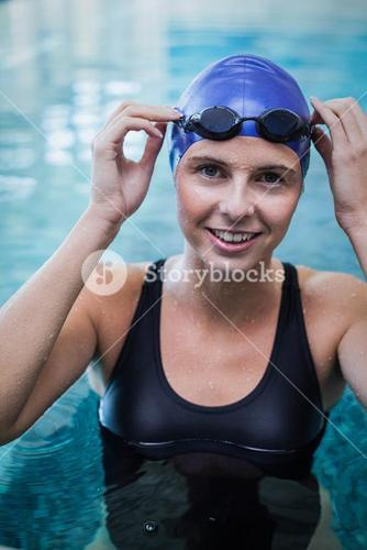 Fit woman wearing swim cap and goggles in the water