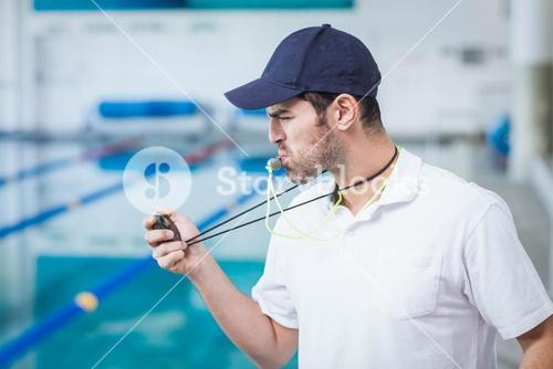Handsome trainer blowing whistle and looking at stopwatch