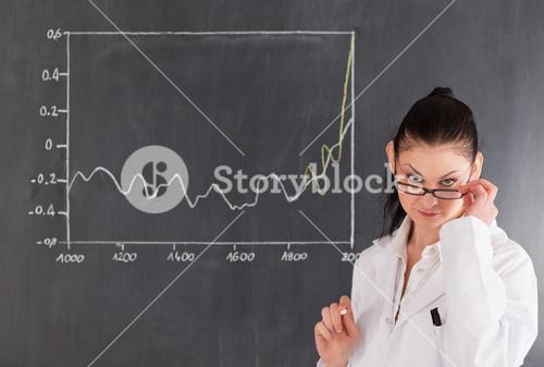 Darkhaired scientist standing near the blackboard