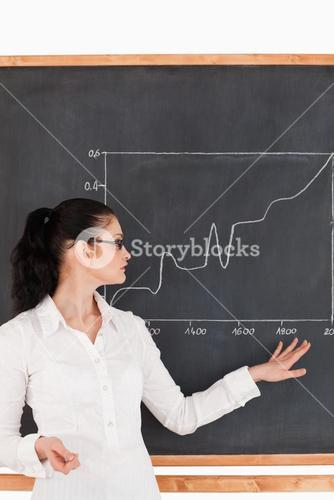 Darkhaired teacher explaining a graph to students