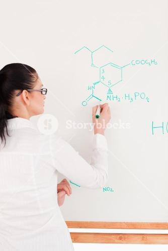 Scientist writing a formula on a whiteboard