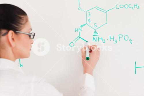 Darkhaired scientist woman writing a formula on a white board