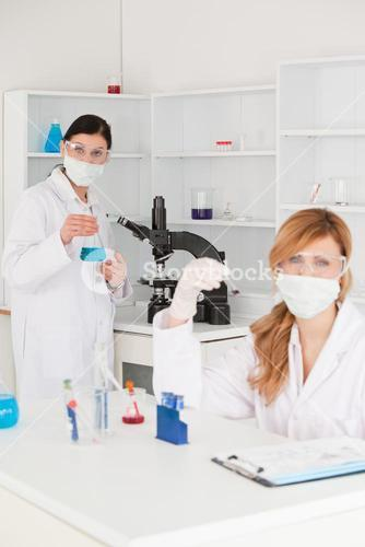 Blonde and darkhaired scientists posing in masks