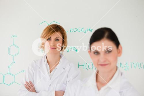 Two women posing in front of a whiteboard