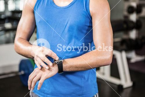 Mid section of handsome man using smartwatch