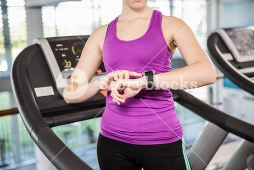 Mid section of fit woman using smartwatch on treadmill