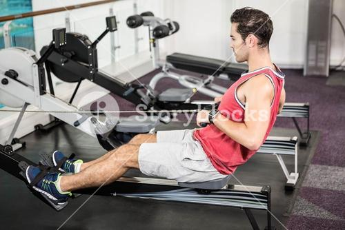 Muscular man on rowing machine