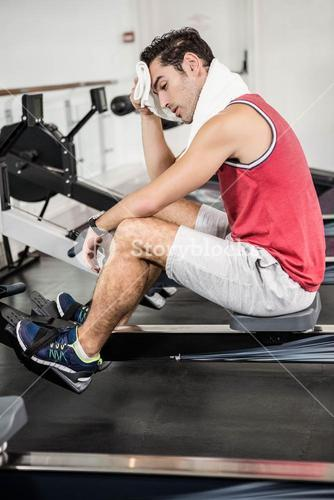 Muscular man on rowing machine wiping sweat with towel