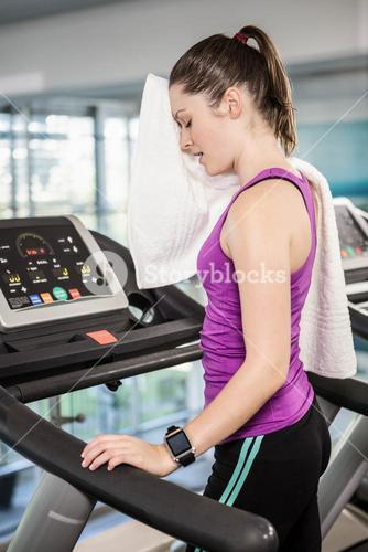 Tired woman on treadmill wiping sweat with towel