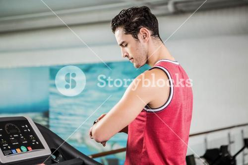 Serious man on treadmill looking at smart watch