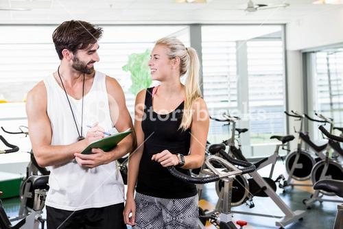 Fit trainer and woman talking