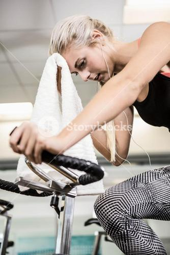 Fit woman on exercise bike wiping sweat with towel