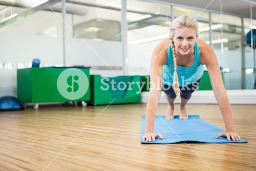 Fit blonde planking on mat