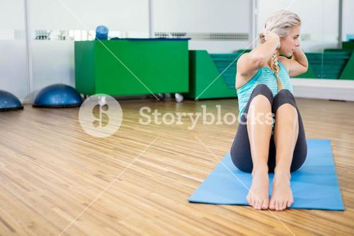 Fit blonde doing sitting up on mat