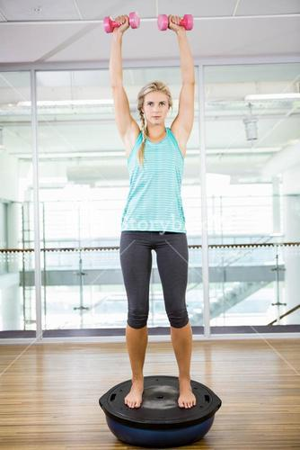 Fit blonde standing on bosu ball and lifting dumbbells