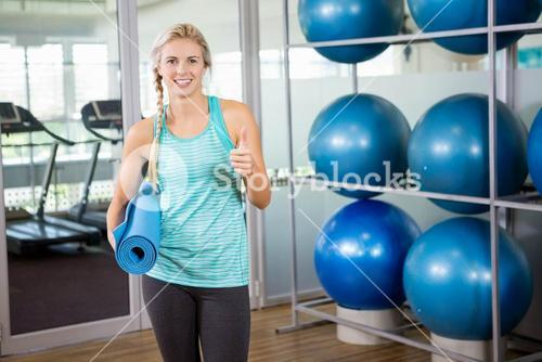 Fit blonde holding mat and showing thumb up