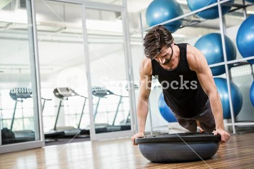 Serious man doing exercise with bosu ball