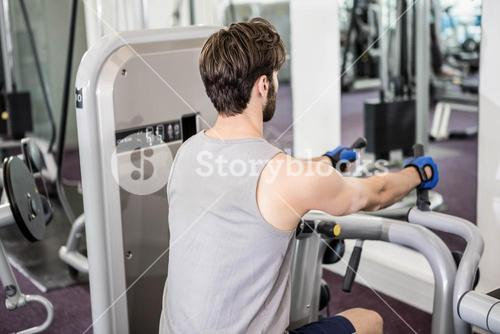 Focused man using weights machine for arms