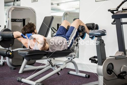 Man doing abdominal crunches on bench
