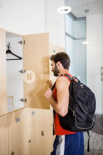 Smiling man opening locker