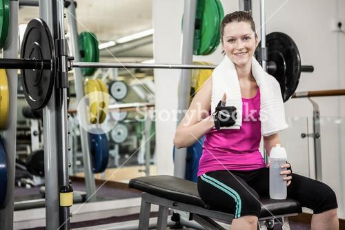 Smiling woman sitting on barbell bench and showing thumb up