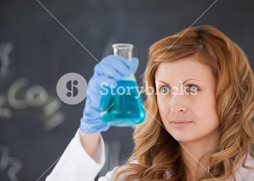 Cute female scientist carrying out an experiment