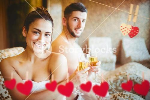 Composite image of happy couple celebrating with champagne