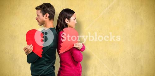 Composite image of serious couple standing back to back