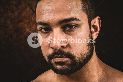 Composite image of muscular man frowning at camera
