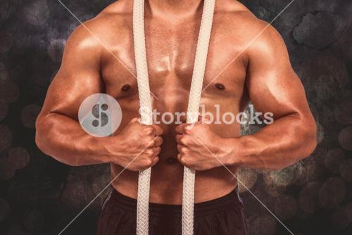 Composite image of muscular man with battle rope