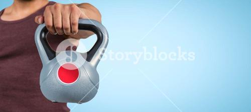 Composite image of mid section of a muscular man holding a kettlebell