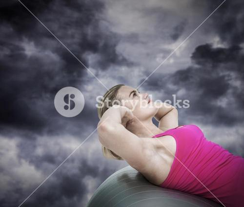 Composite image of muscular woman exercising on ball