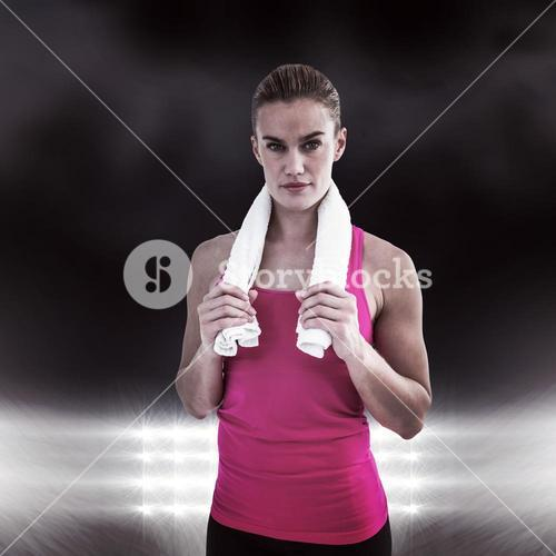 Composite image of muscular woman holding a towel around her neck