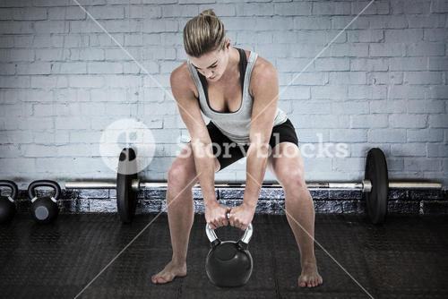 Composite image of serious muscular woman lifting kettlebell