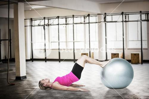 Composite image of side view of woman exercising with ball