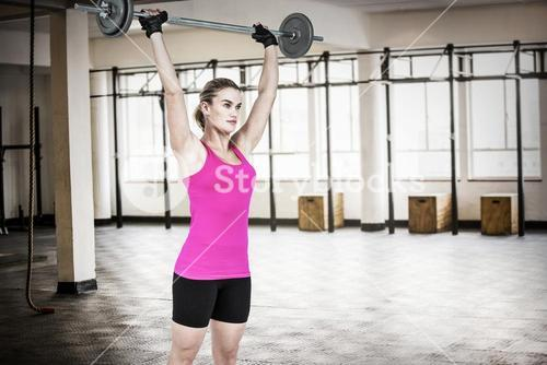 Composite image of sporty female bodybuilder lifting barebell