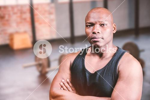 Composite image of portrait of bald bodybuilder with arms crossed