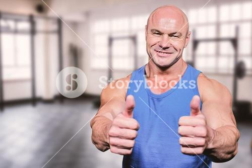 Composite image of smiling healthy man showing thumbs up